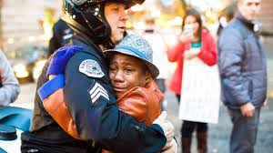 White officer -- one of the good guys -- hugs a black boy who is crying from fear that police officers might kill him because he's black. Officer Bret Barnum and Devonte Hart.